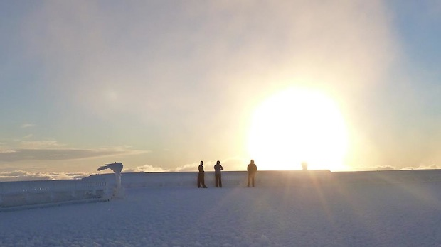 Our Summit Interns, Tom Padham and Sam Hewitt, take in a sunrise atop the rime- and snow-covered observation deck, along with Director of Summit Operations Cyrena Briedé. - Mt. Washington Observatory