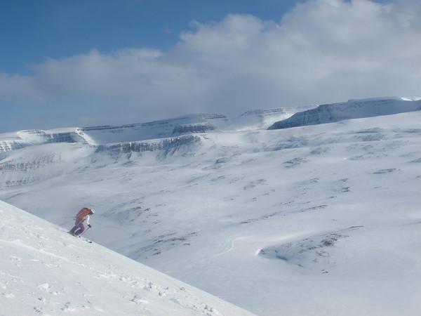 Skiing down.