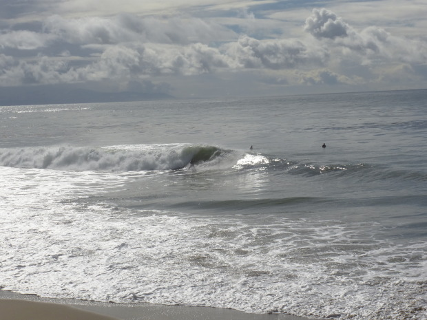 A perfect left at 26th Avenue with a very happy surfer carving up the face.