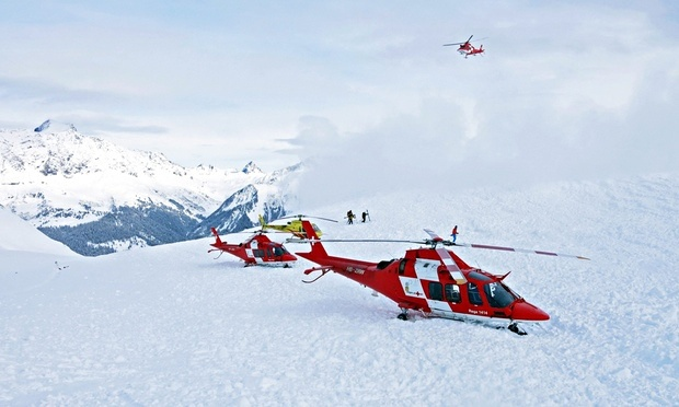 Rescue helicopters and rescue workers on duty after avalanche accident at the Piz Vilan mountain. Photograph: REGA / HANDOUT/EPA