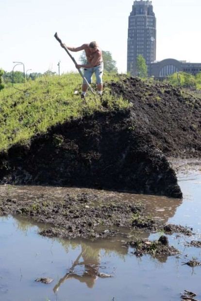 """© AP Photo/Gary Wiepert Robert A. Raczka uses a stick on top of this dirt-covered snow """"glacier"""" that still hasn't melted at the Central Terminal on Buffalo's East side eight months ago, Tuesday, July 28, 2015."""