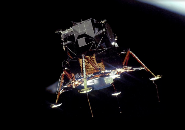 """The Apollo 11 Lunar Module (LM) """"Eagle"""", in a landing configuration is photographed in lunar orbit from the Command and Service Modules (CSM) """"Columbia"""". Inside the LM were Commander, Neil A. Armstrong, and Lunar Module Pilot Edwin E. """"Buzz"""" Aldrin Jr. The long """"rod-like"""" protrusions under the landing pods are lunar surface sensing probes. Upon contact with the lunar surface, the probes send a signal to the crew to shut down the descent engine."""