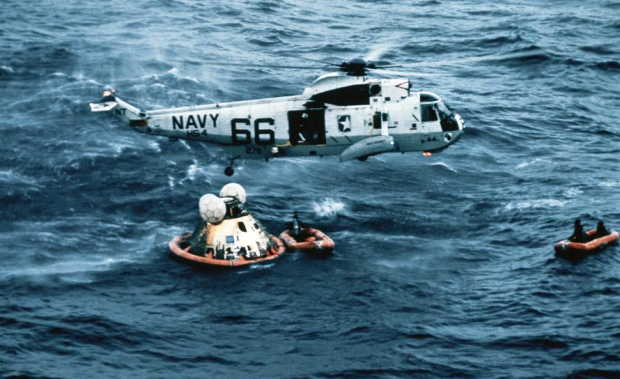 Apollo 11 crew boarding a recovery helicopter after a successful splashdown on July 24, 1969