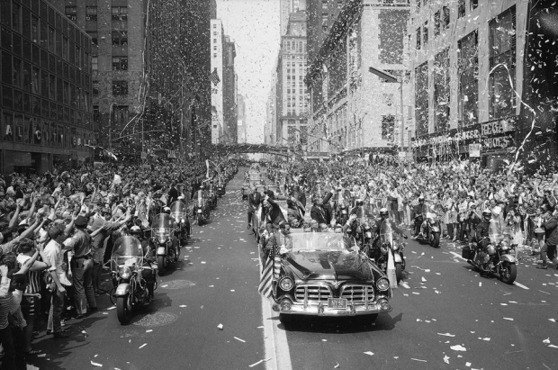 New Yorkers line 42nd Street to cheer Apollo 11 astronauts on August 13, 1969. In lead car from left are: Edwin Aldrin, Michael Collins and Neil Armstrong, who return the greeting with waves. Motorcade is traveling East on 42nd street, towards the United Nations building. #