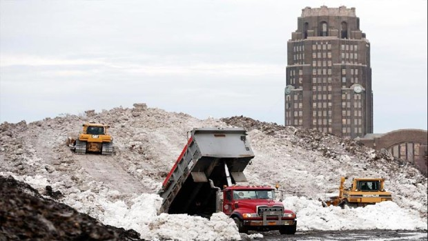 Dump trucks pile snow at Buffalo's Central Terminal on Sunday, November 23, 2014 after a lake effect snow storm brought over seven feet of snow