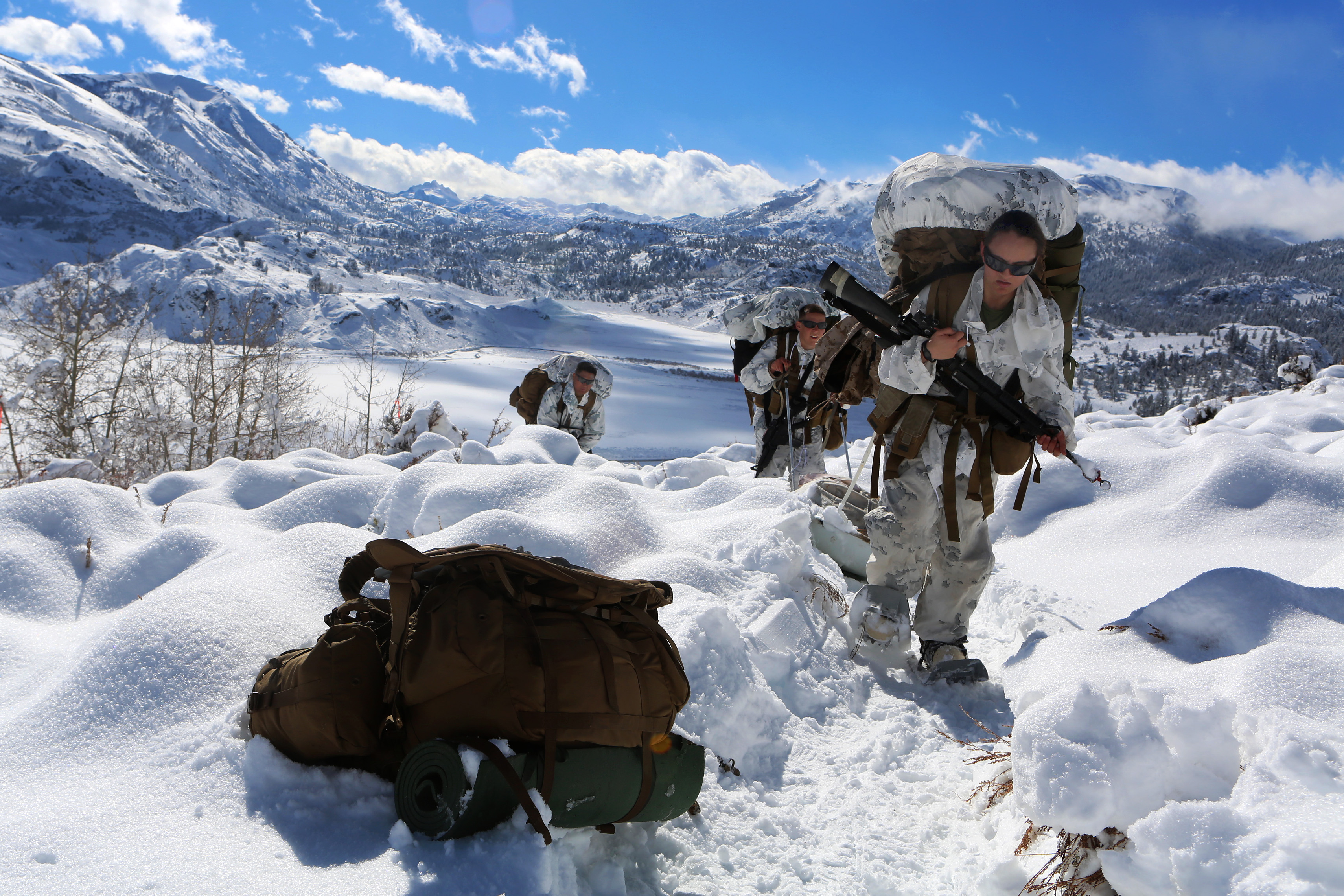 Marine Corps Lance Cpl. Eleanor H. Roper, front, pulls a weather infantry kit up a slope during a field exercise on Marine Corps Mountain Warfare Training Center in Bridgeport, Calif., Jan. 31, 2014.