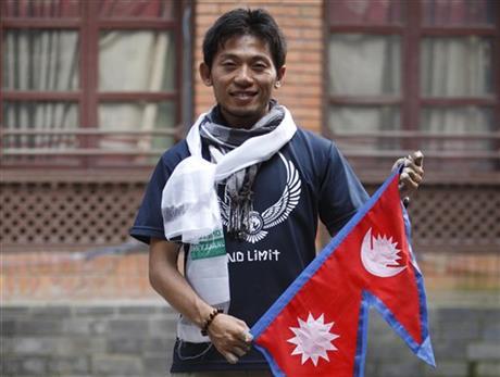 Nobukazu posing with the Nepali flag at a press conference in Katmandu. photo: AP Photo/Bikram Rai