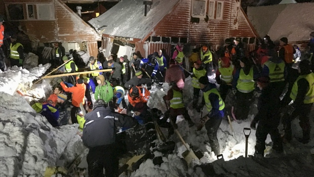 Search and rescue crews work after an avalanche hit several houses in Longyearbyen, Norway, Saturday Dec. 19. 2015. It is unclear about the number of people caught in the avalanche but authorities are calling for volunteers with shovels to help in the search to locate victims. (NTB scanpix via AP)