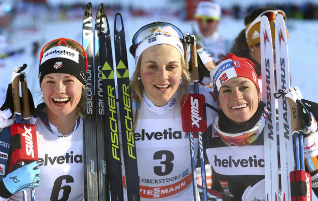 Sweden's Stina Nilsson is flanked by second placed Jessica Diggins from the US, left, and third placed Heidi Weng from Norway after Nilsson won the women's skiathlon at the FSI Tour de Ski cross country competition in Oberstdorf, Germany, Jan. 3, 2017. (Karl-Josef Hildenbrand/dpa via AP)