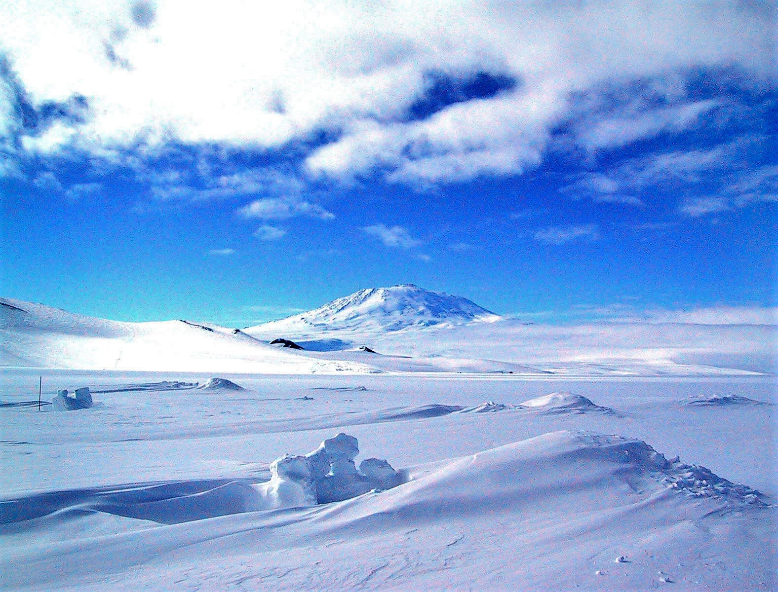 The Antarctic Ice Sheet covers an area larger than the U.S. and Mexico combined. This photo shows Mt. Erebus rising above the ice-covered continent. Credit: Ted Scambos & Rob Bauer, NSIDC