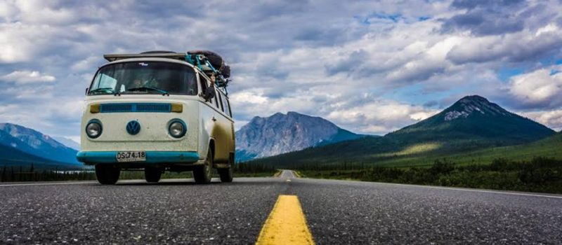A VW van coasting below the mountains.
