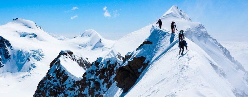 Mountaineers make their way across a snowy ridge.