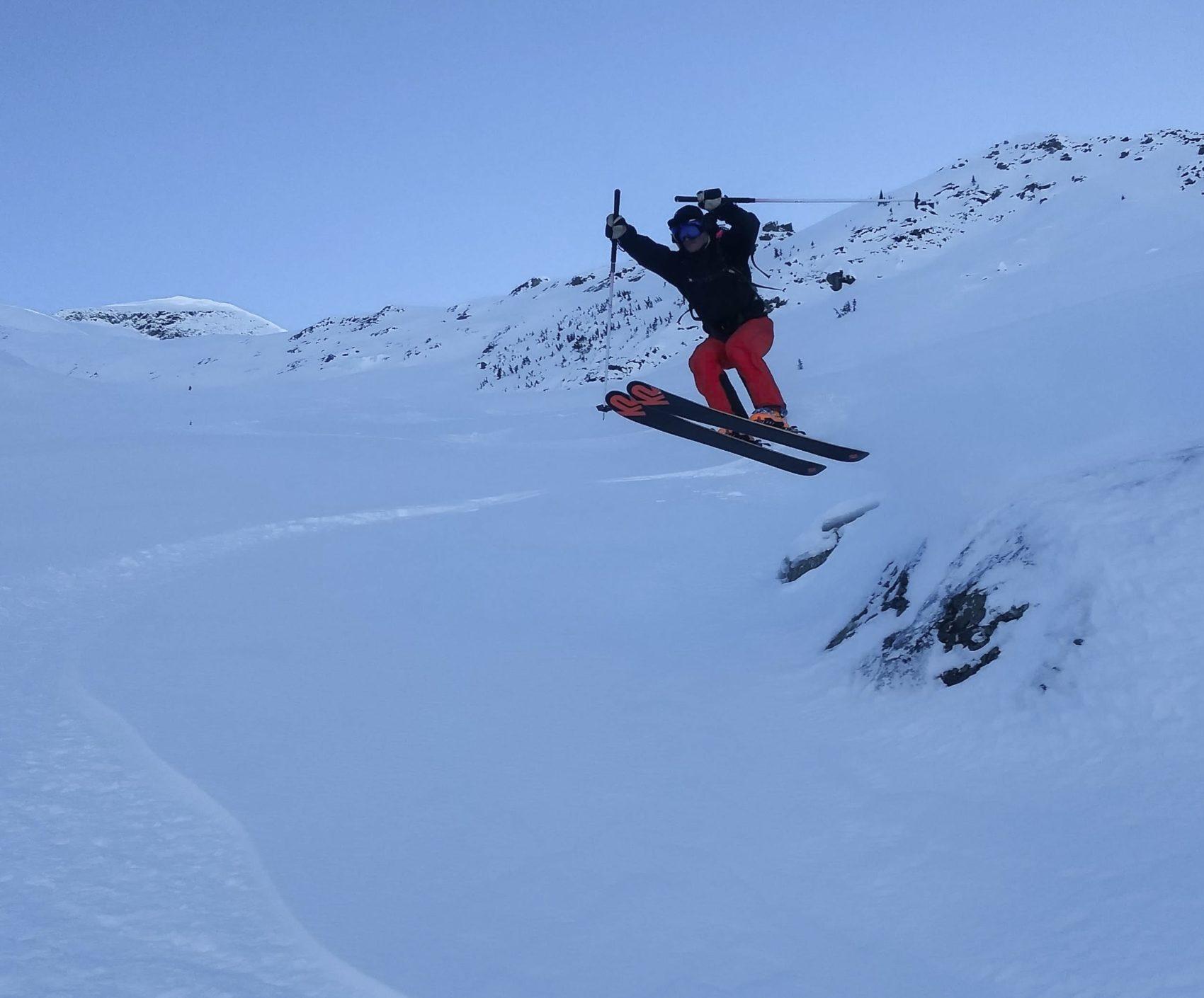 skier leaping off boulder