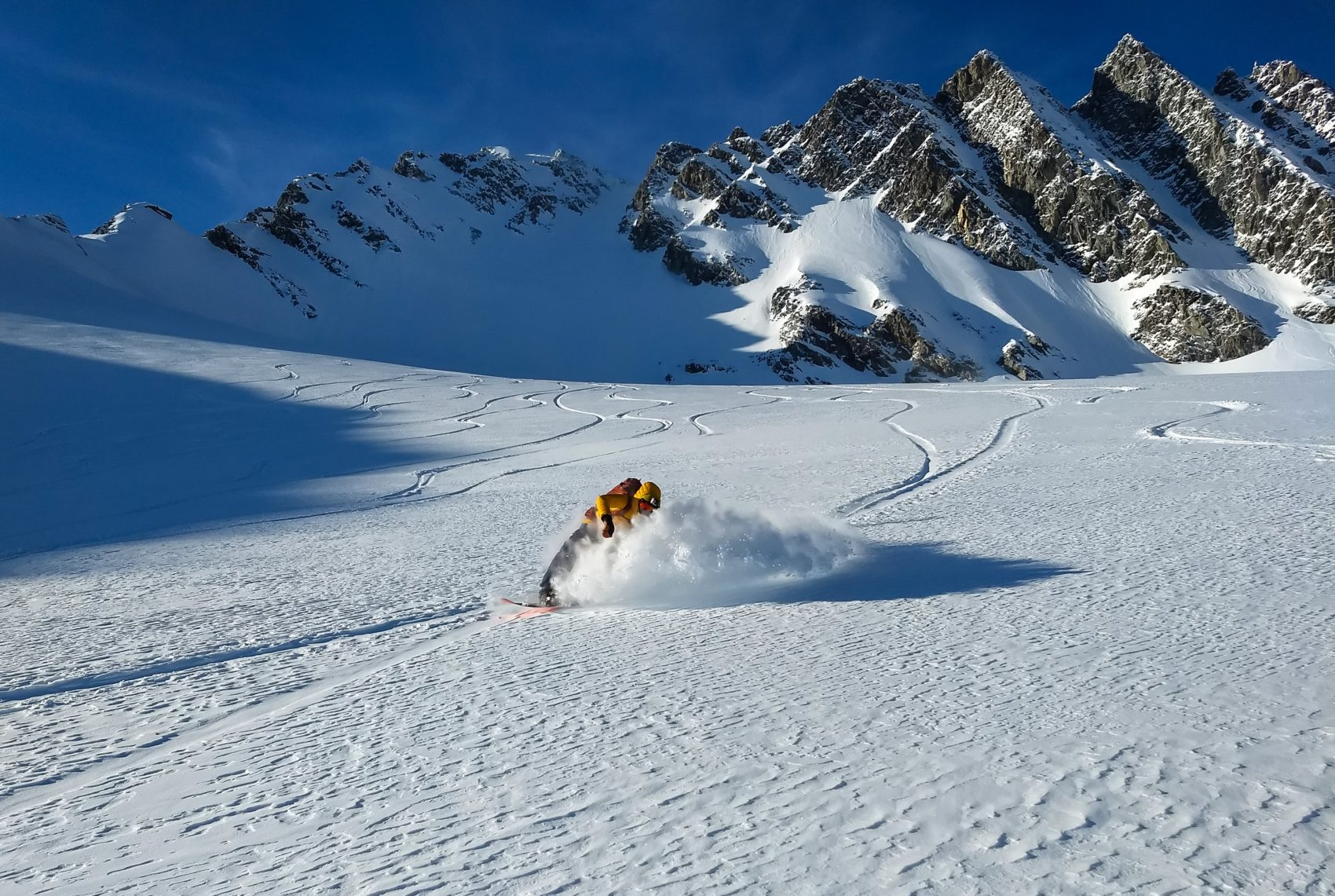 snowboarder carving through snow on swiss glacier