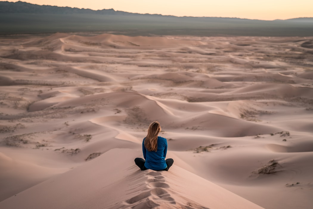 Woman achieves mindfulness practicing meditation on some amazing dunes.