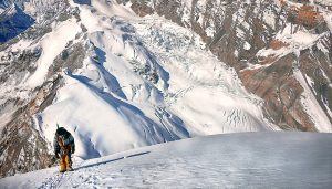 Mountain climber is shown on an exposed slope, high above a glacier.