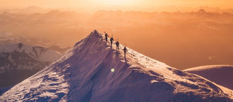 hikers climb peak in winter with back country skis
