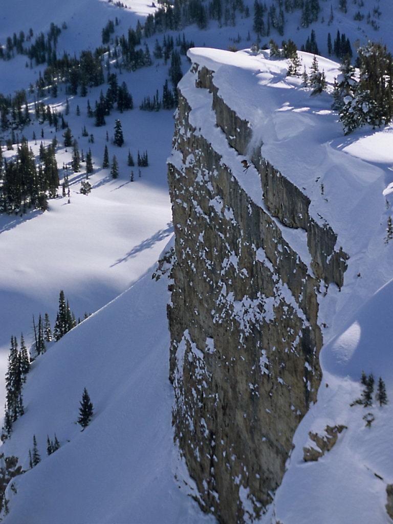 Cliff jump ski snow powder ski send BASE jump