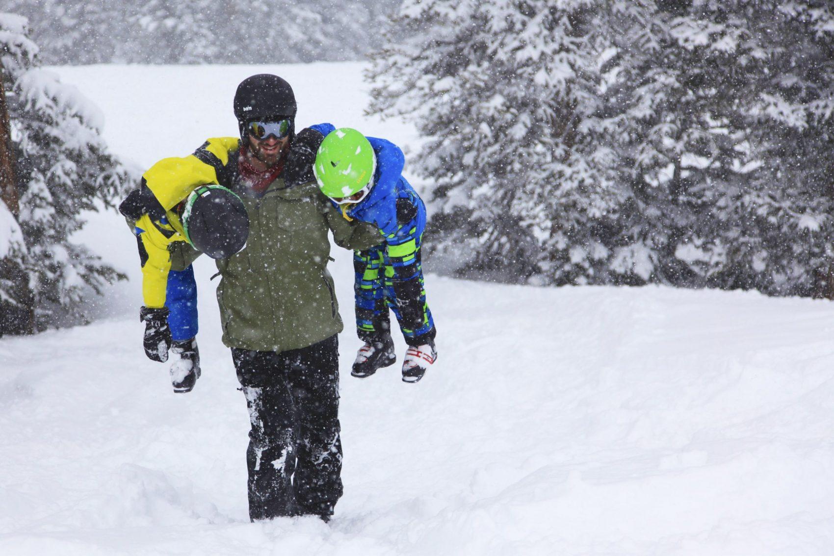 ski instructor carrying kids