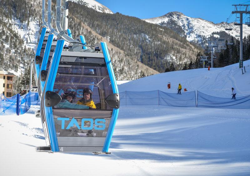 people riding taos ski lift, app