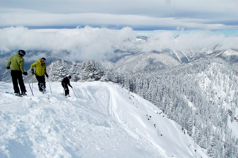 Skiers overlooking drop, Taos, app,